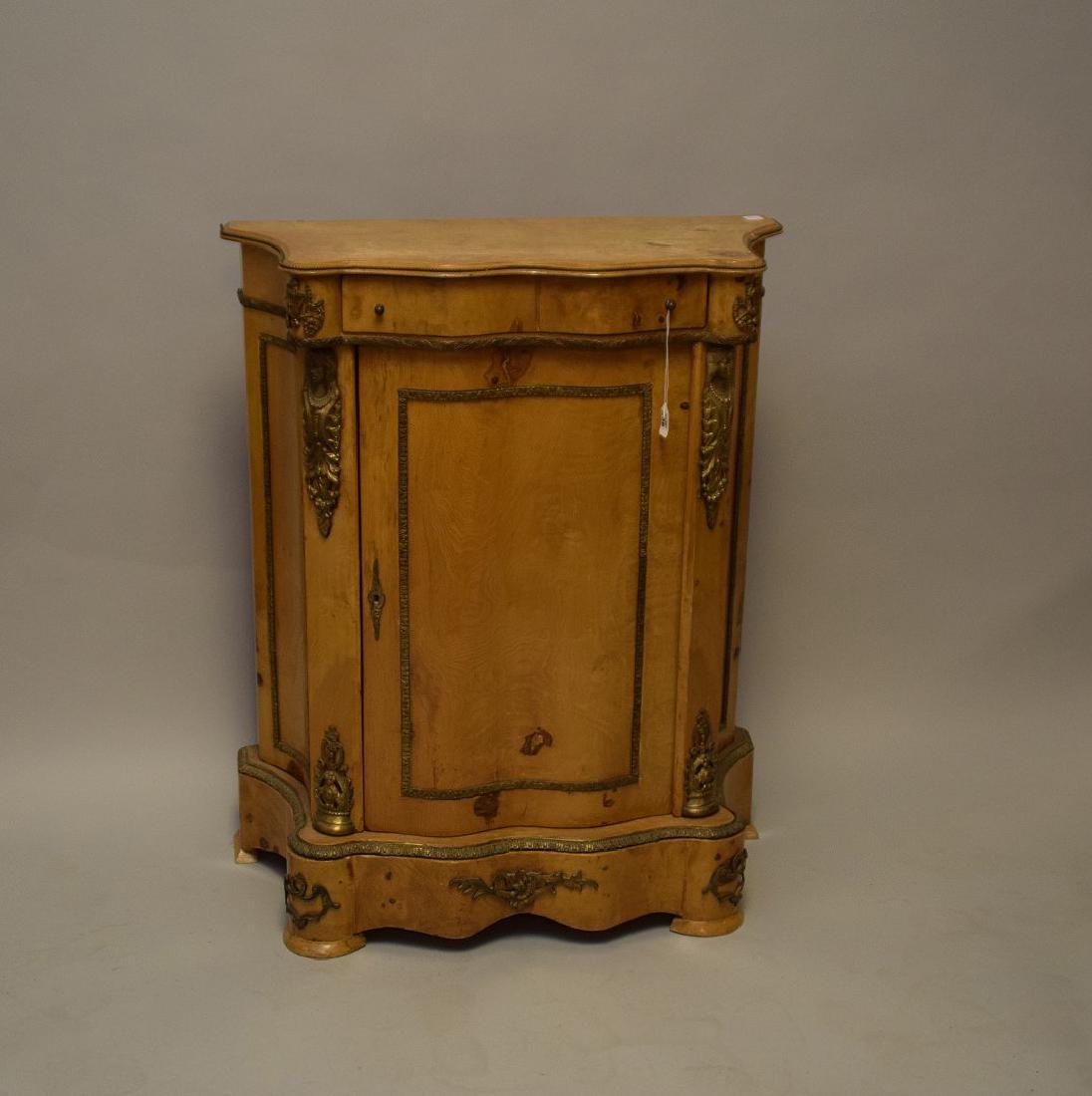Light wood French serpentine cabinet with gilt metal