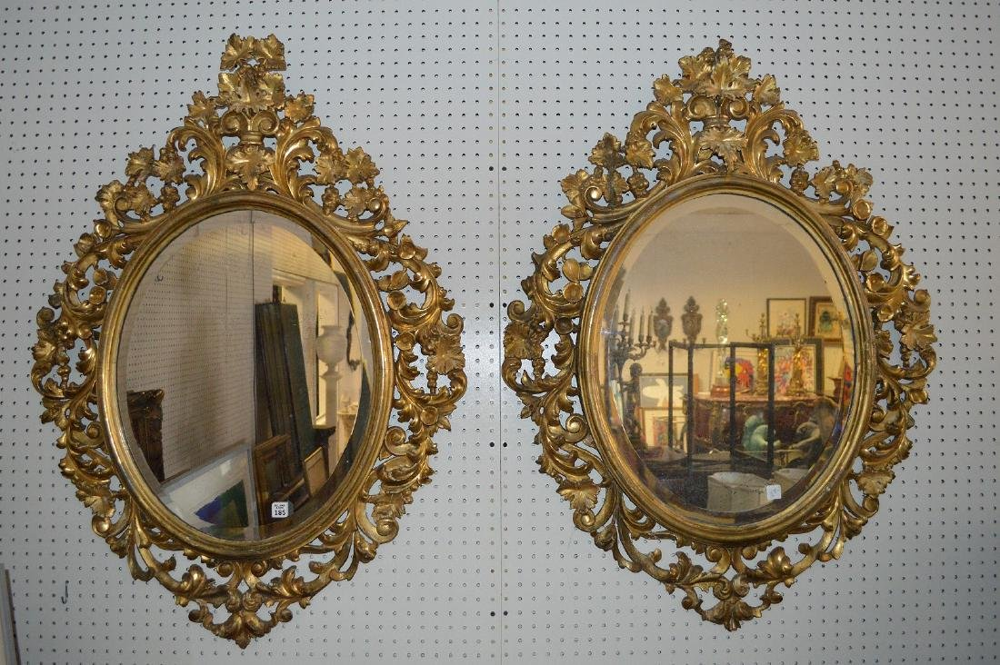 Pair of oval giltwood leaf & scroll carved mirrors,