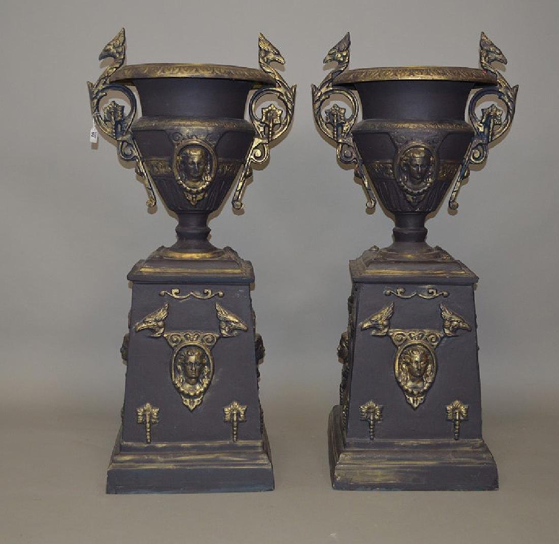 Pair black painted iron urns on pedestals with slight