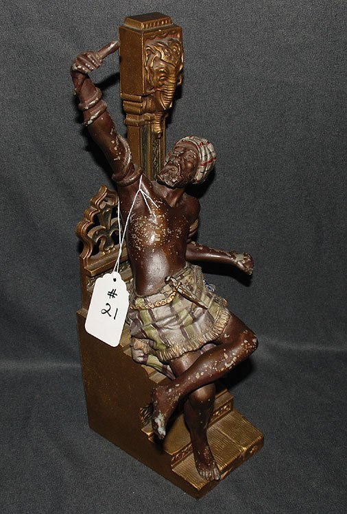 21: Bronze seated figure with snake wrapped around his