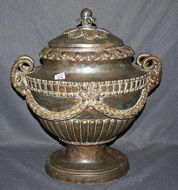 11: Bronze urn, heavily decorated, ram's head and garla