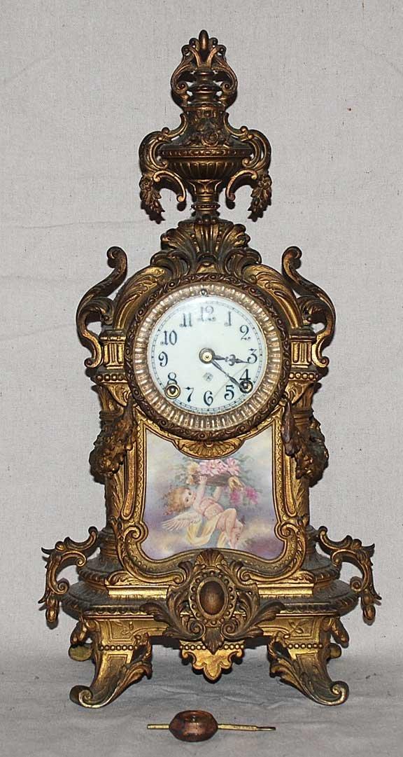 1013: Bronze Clock, cherub painted porcelain  insert at