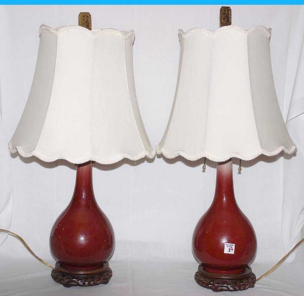 1: Pair of ceramic dark red lamps on carved Oriental wo