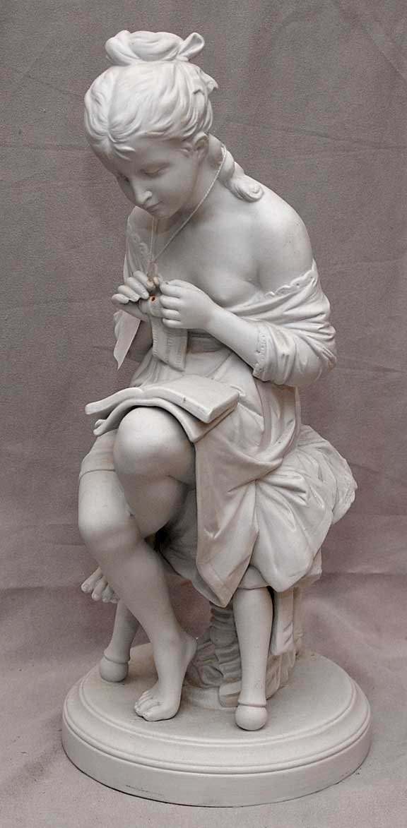 "12: ""Germany"" figurine of girl reading on attached stan"