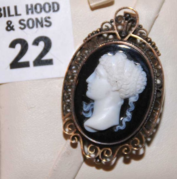 22: Carved cameo on black background, filigree pin / pe