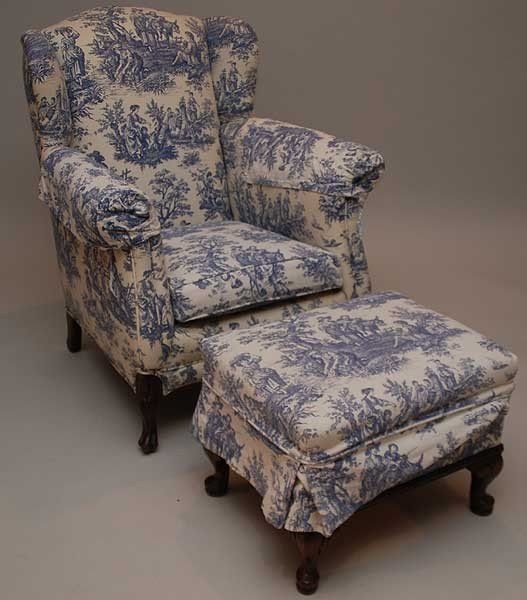 70: Small wing back chair and ottoman with blue toile f