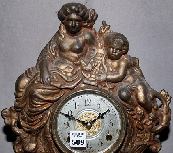 "509: Cast iron figural wall clock with putti, 17""h, wor"