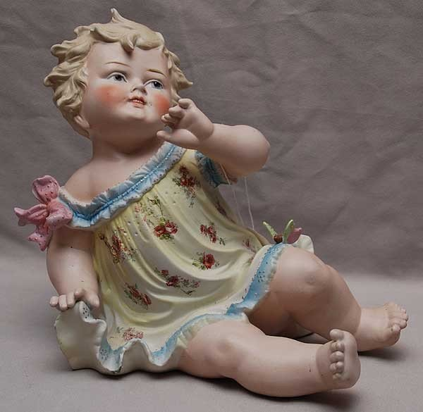 "19: ""Germany"" Piano Baby, figurine of child, butterfly"