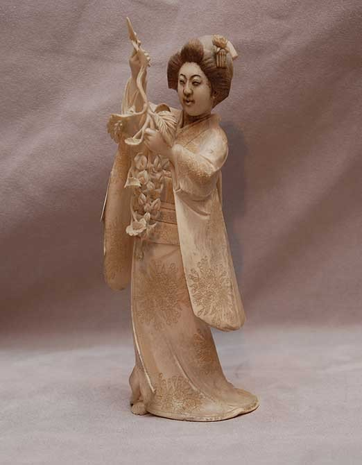 16: Chinese Carved ivory girl with vine & tendrils in h