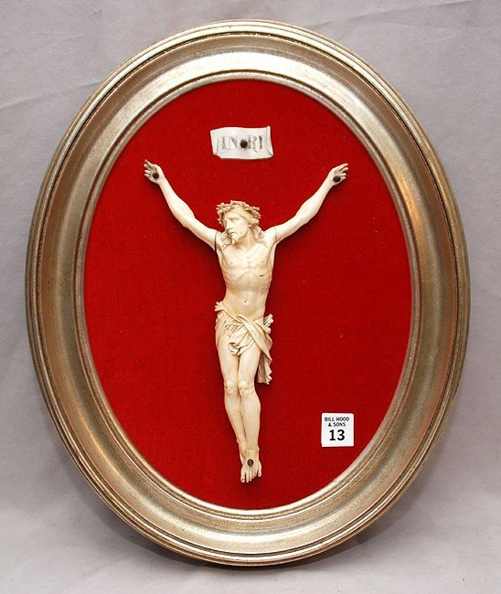13: Carved ivory crucifix on red velvet in silvered ova