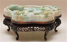 Carved jade bowl with floral designs sitting on a