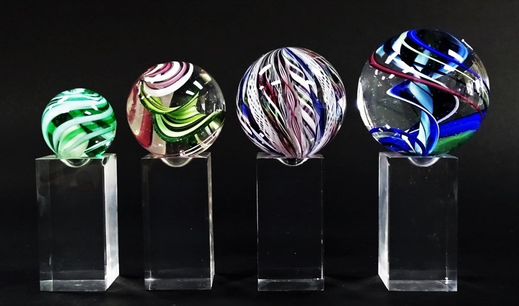 GROUP OF 4 SIGNED ART GLASS ORBS ON STANDS