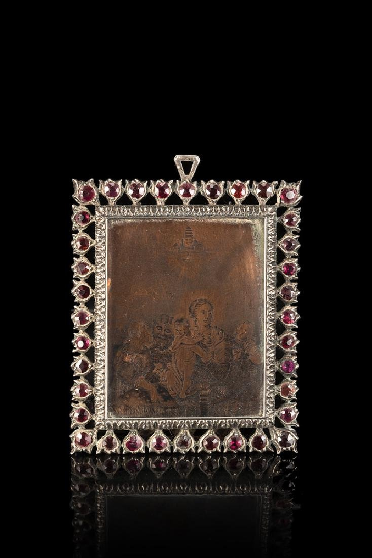 A small silver frame with Holy Family engraved on