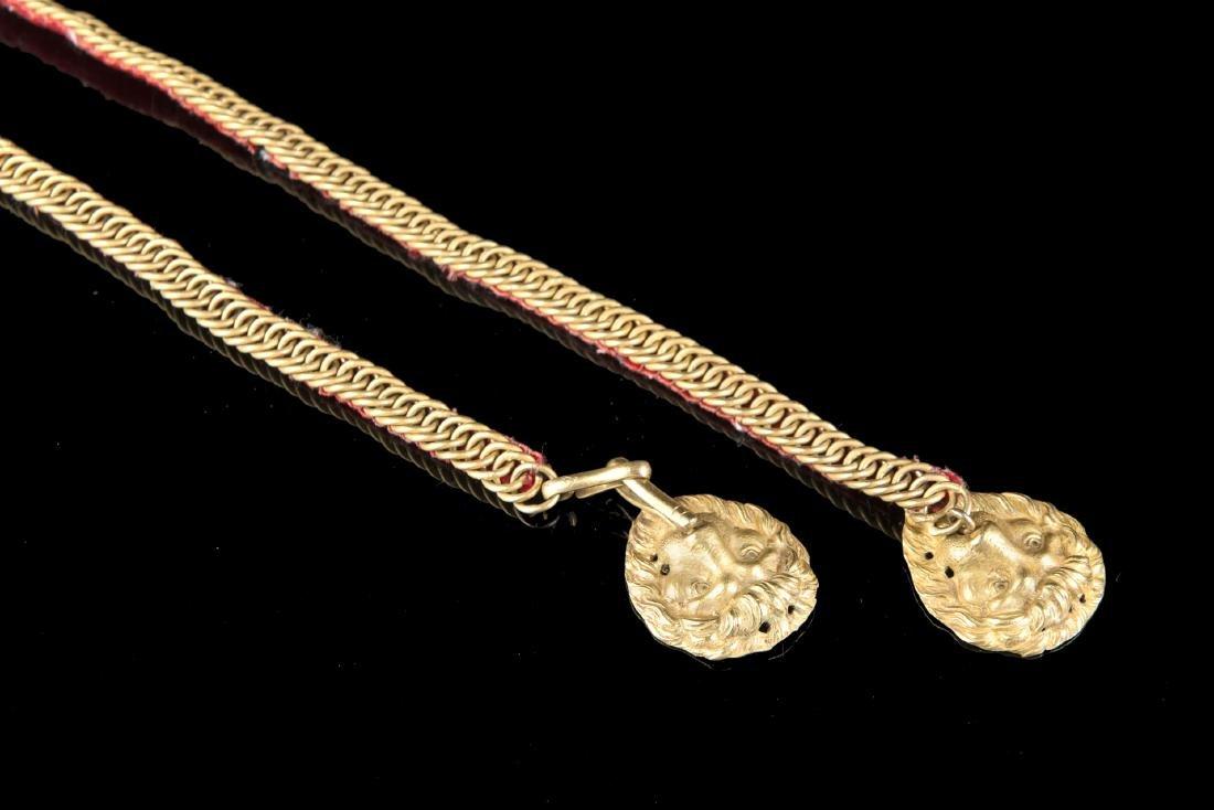 Mascheroni di teste leonine in metallo dorato al