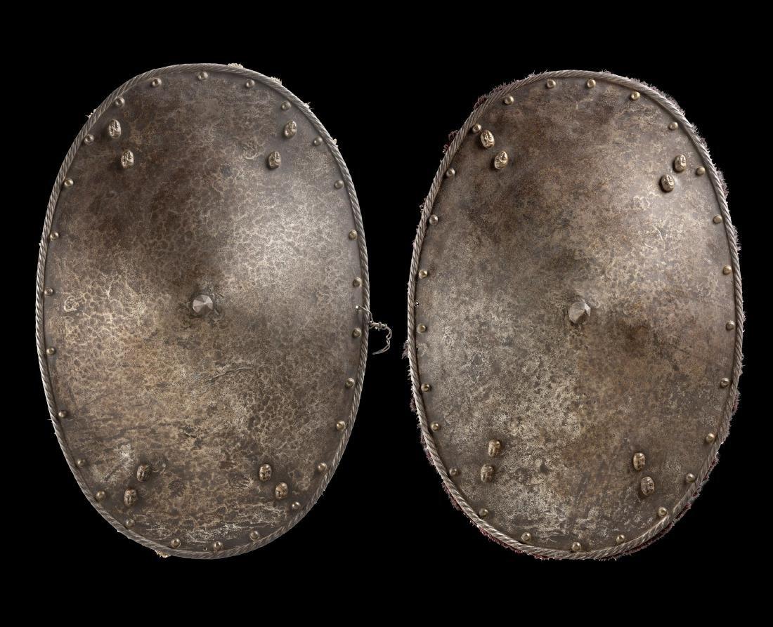 Coppia di scudi ovali in ferro martellato con una