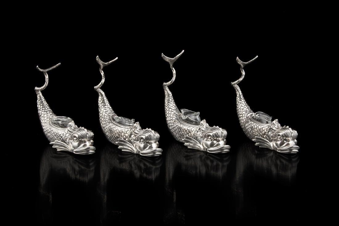 * Quattro saliere in argento modellate in figura di