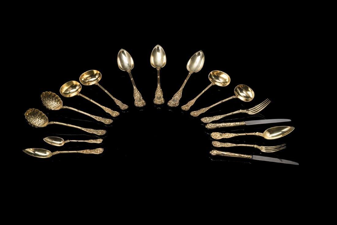Servizio di posate similari in argento dorato decorate