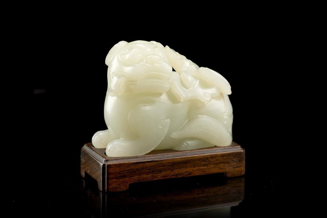A pale celadon jade model of a Buddhist lion, wood base