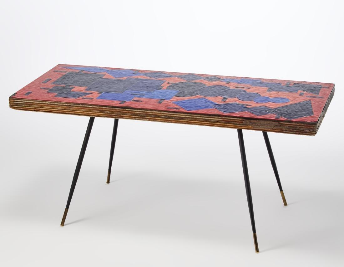 Tavolo basso con piano rivestito da un pannello in rame