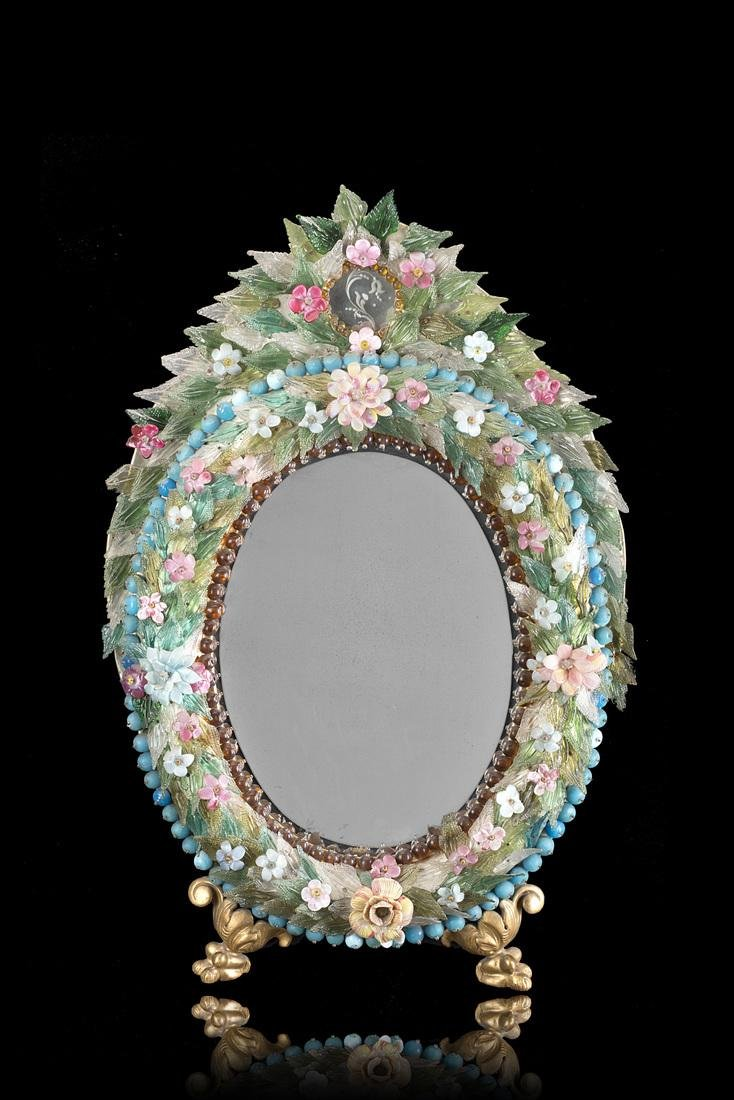 An oval glass paste and glass mirror with giltwood