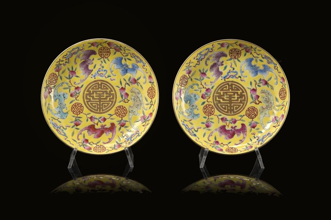 A pair of yellow-ground Famille Rose saucers, each