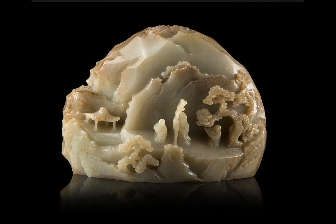A large celadon jade boulder carved and pierced with a