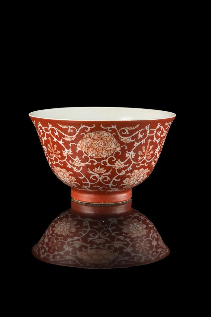 A small coral red cup decorated with floral motifs in