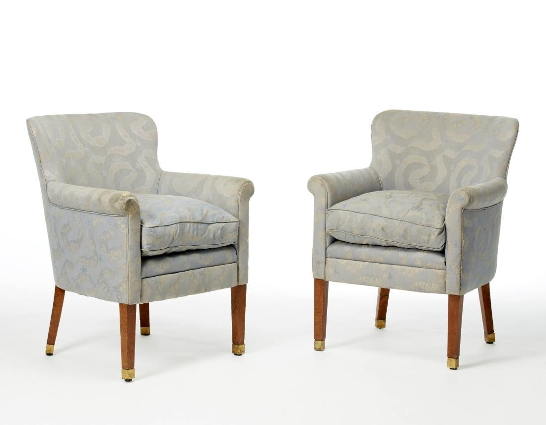 Pair of armchairs with high legs and brass tips in