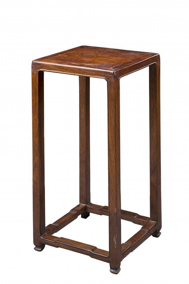 A tall four legged pierced wood stool