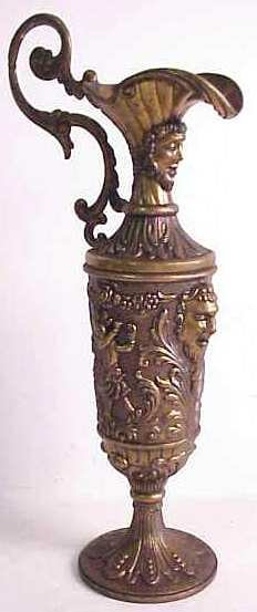 1031: Figural bronze coated spelter ewer with heads and