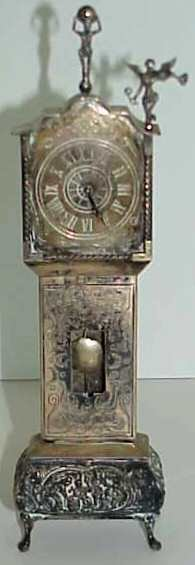 29: CONTINENTAL SILVER MINITURE TALL CASE CLOCK, CHERUB