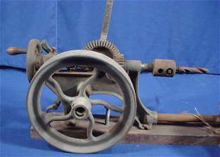 Early bench mounted drill press with iron fly whe