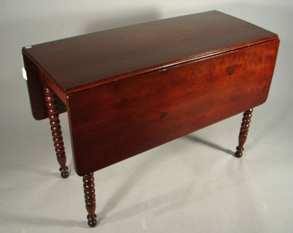 12: Mahogany drop leaf table with exaggerated spool leg
