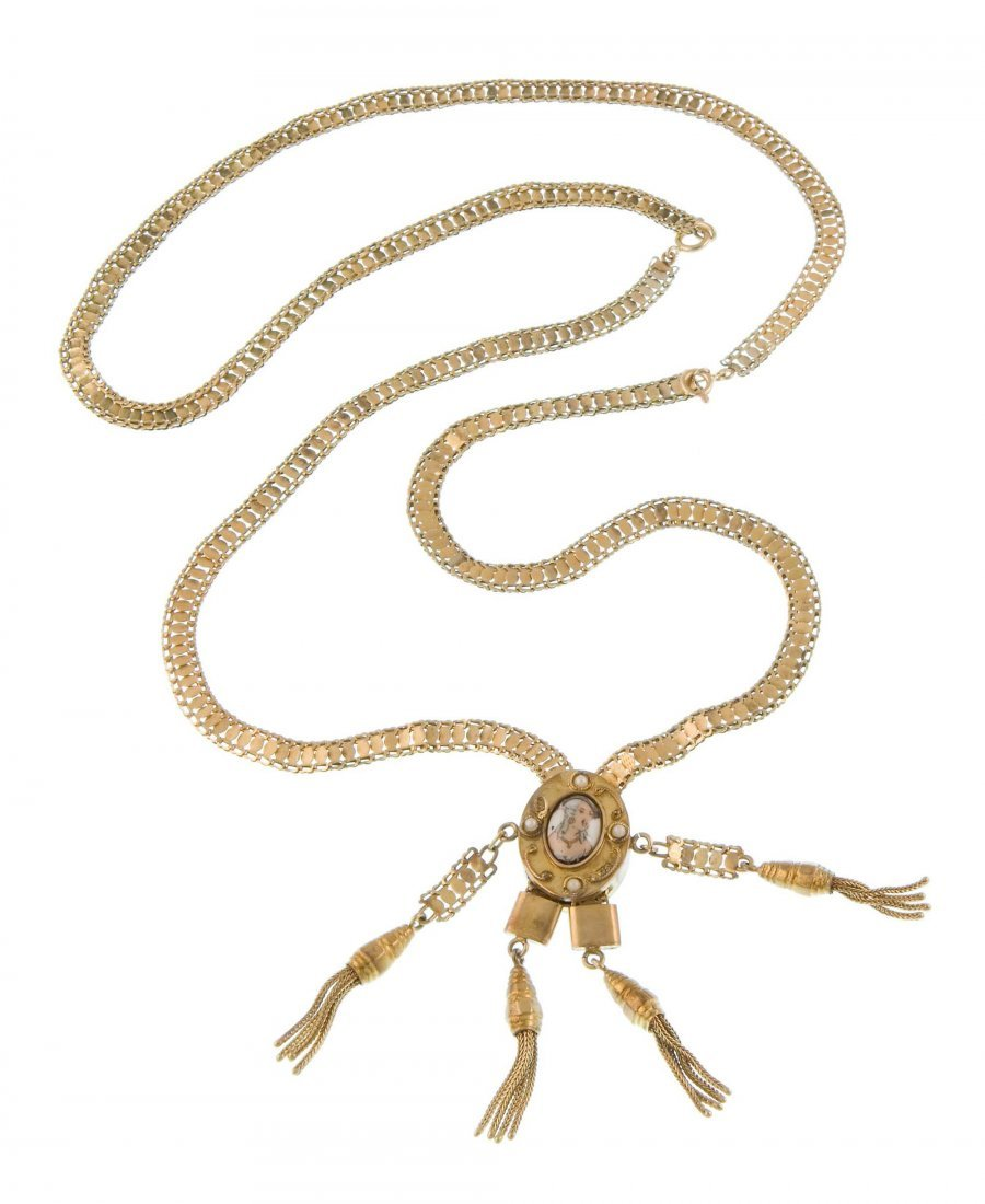 A gold necklace with a medallion and tassel pedants