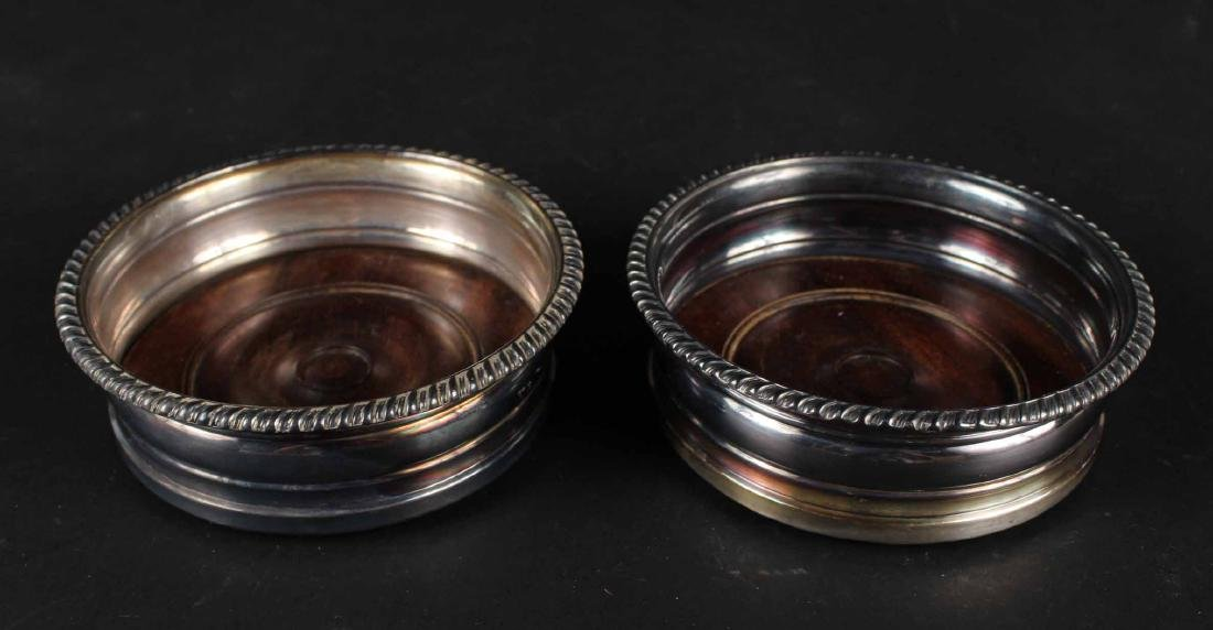 TWO SILVER PLATED WINE BOTTLE COASTERS