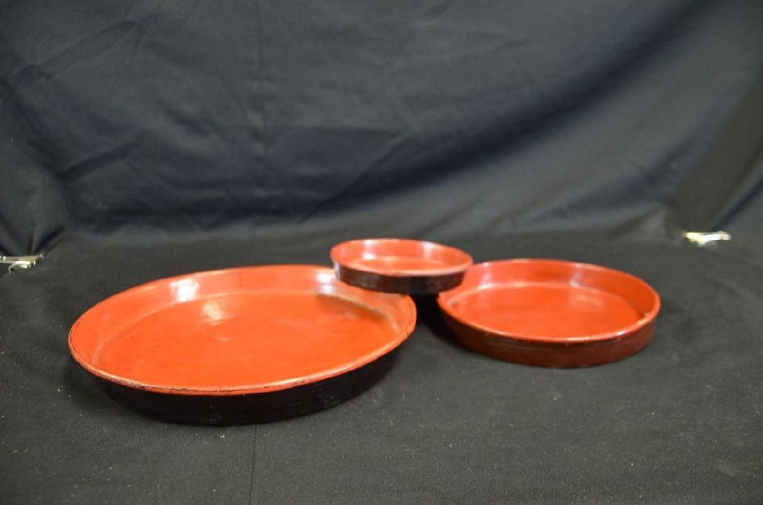 Lot de trois assiettes en laque rouge, pourtours peints