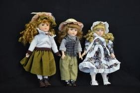 Collection of three dolls with porcelain heads.