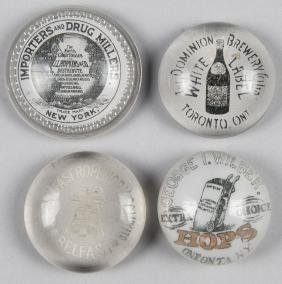 Four circular advertising paperweights, largest -