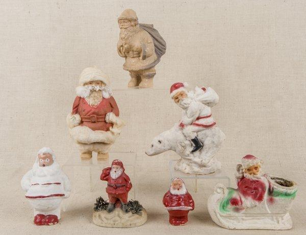 Collection of seven cardboard Santa candy contain