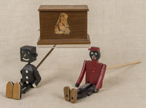Two black Americana dancing toys, together with a