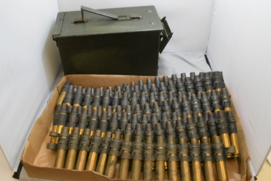 BOX WITH 4 STRIPS OF EMPTY .50 CAL CASINGS AND A M