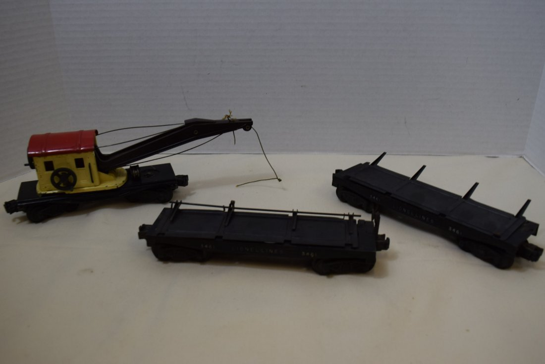 2 LIONEL LOG UNLOADING CARS AND ONE CRANE