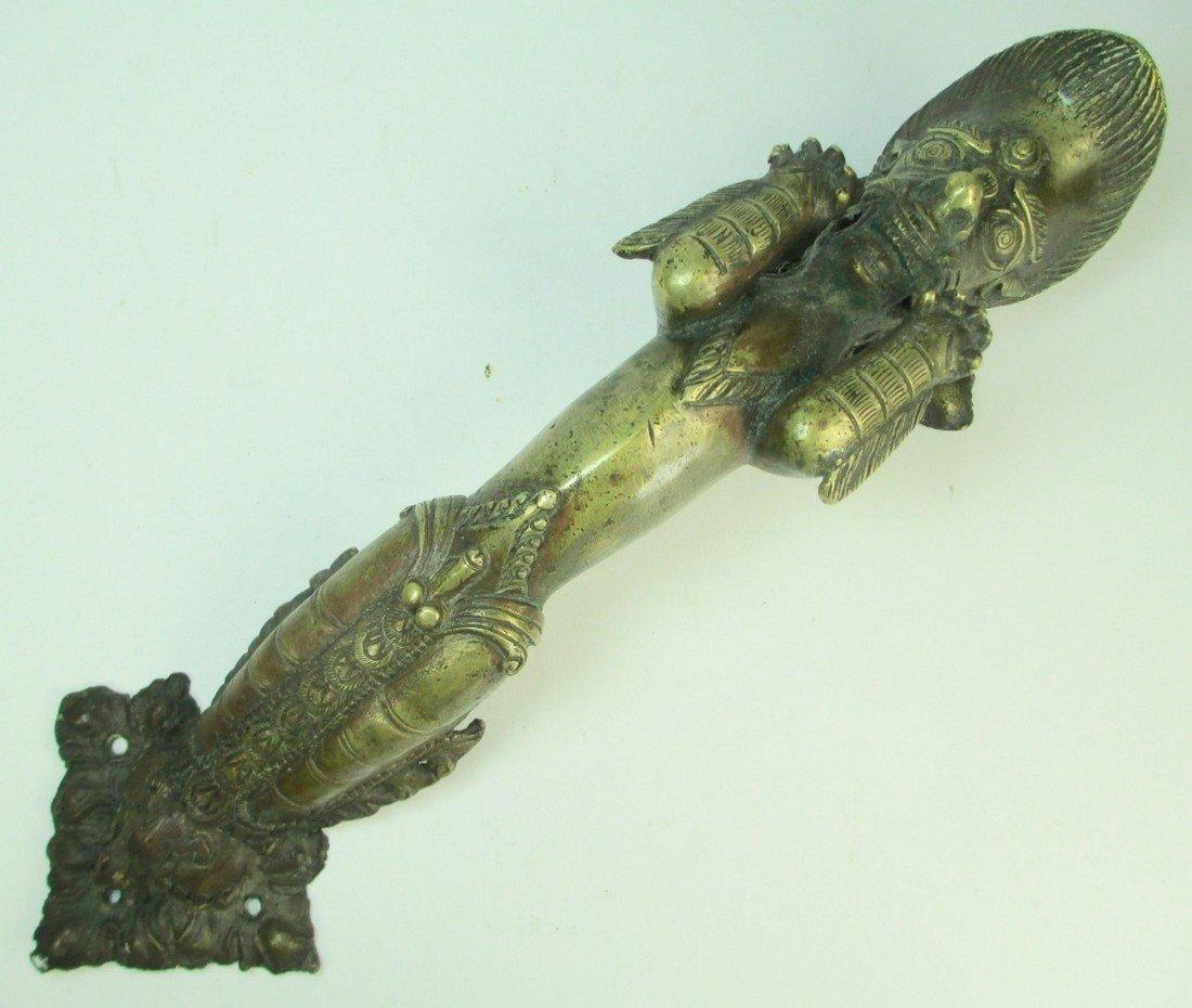 An unusual brass door handle