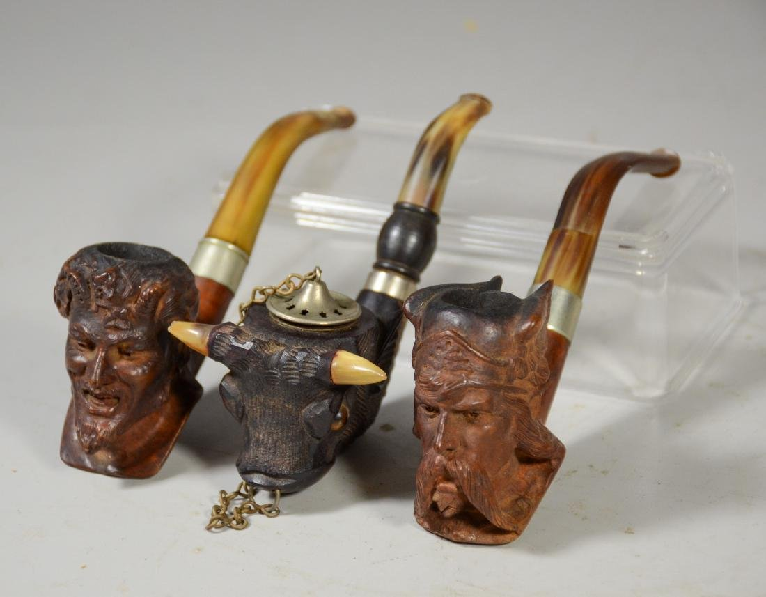 Three (3) carved Meerschaum type pipes, one of a Viking