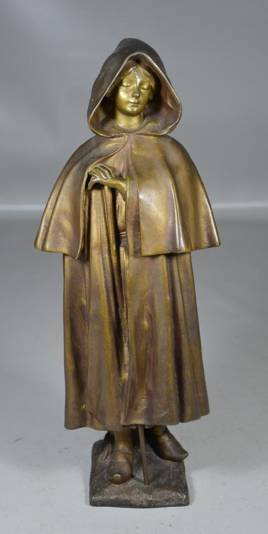 Bronze tone spelter figure of a woman with cloak,