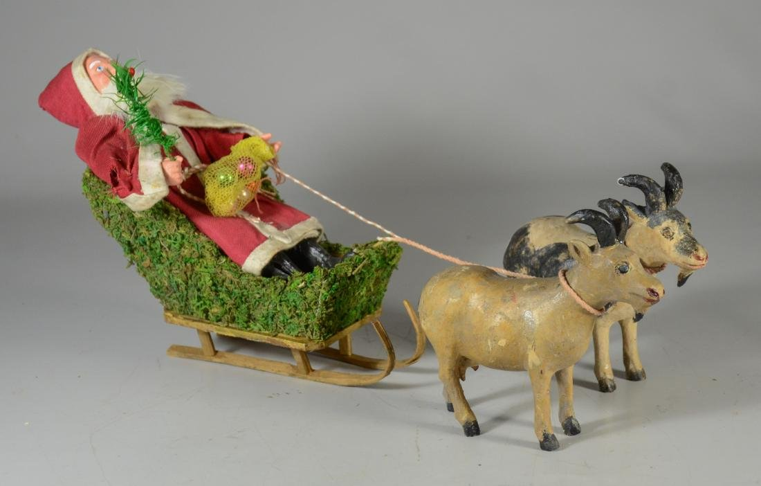 Santa Claus, long red coat riding in goat drawn sleigh