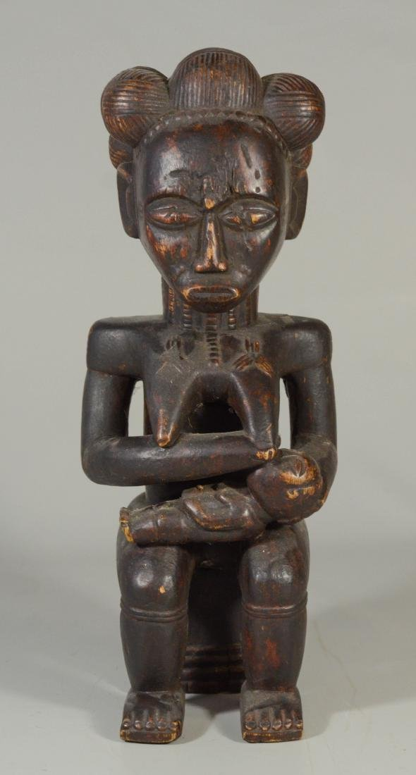 African carved wood figure of nursing mother seated on