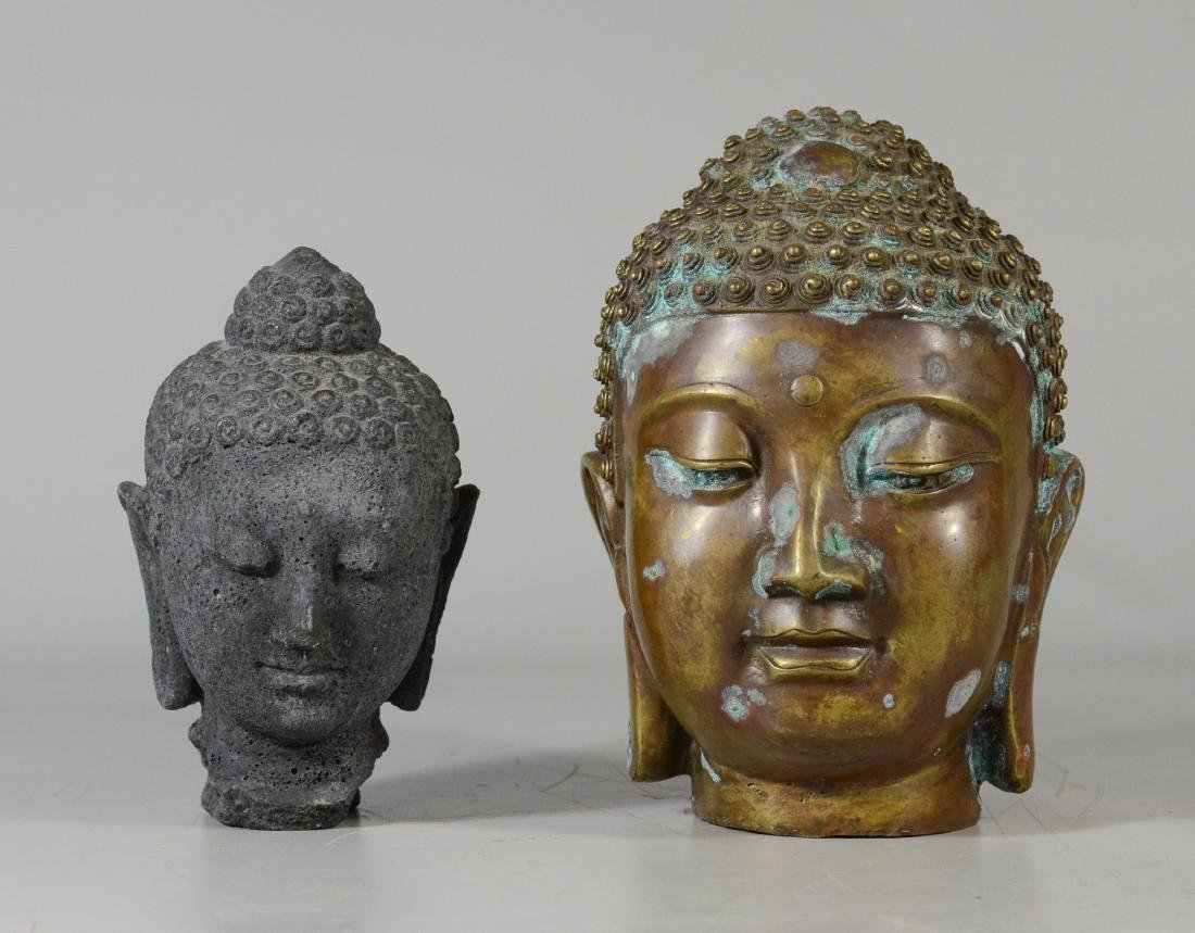 two Buddha heads, one of faux stone and one of brass