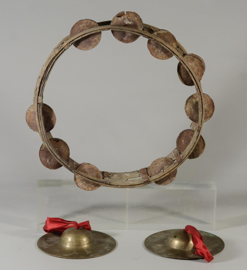 Large primitive tambourine and a pair of hand cymbals