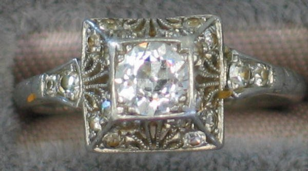 1244: 18K white gold diamond filigree ring with a cente